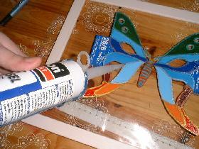 mettre du silicone translucide en épaisseur sous les ailes de manière à maintenir l'effet de relief après séchage. enlever les boites après avoir vérifier si la colle est bien durcie ( attendre une journée)
