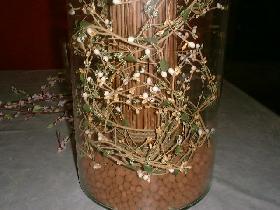 placer la botte de branches ( sans enlever le lien à la base ) dans le vase en la tassant dans les billes pour la maintenir droite <p>entourer la base de la botte avec la guirlande fleurie