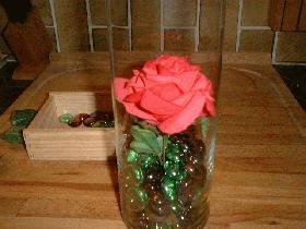 couper la tige de la rose et la placer dans le vase en maintenant la tige dans les billes de verre