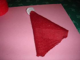 Avec le tissu rouge, découper un demi cercle et former le bonnet. Coller ou coudre. <br /> Au bout de celui-ci, coller une boule de coton